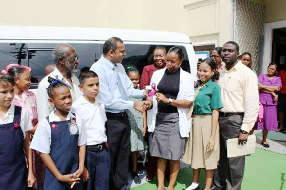 Minister of Culture, Youth and Sport, Dr. Frank Anthony presents keys to the vehicle to the Assistant Secretary, (Admin) of the Culture, Youth and Sport Ministry, Alexis Sullivan. (GINA photo)