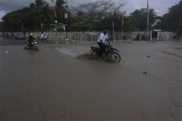 Motorcyclists drive along the flooded roadway at the University of Guyana junction yesterday. (Photo by Arian Browne)