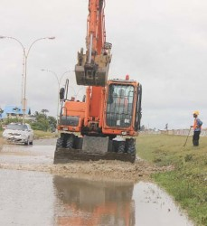 To the rescue: Heavy machinery from the Ministry of Works helping with the clean-up operation along the East Coast highway yesterday.