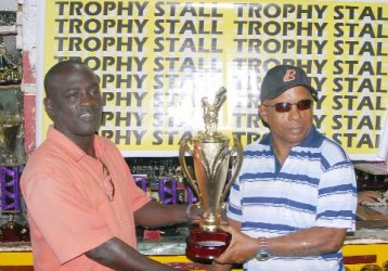 Marlon Washington (left) receives the first place trophy for the upcoming Premium Beer Futsal Classic tournament on behalf of Unique Entertainment yesterday from a representative of the Trophy Stall. (Orlando Charles photo)