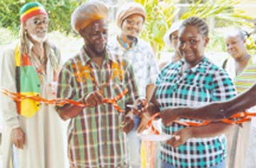 Akeela  Sheena Gilgeous cuts the ribbon during the ceremony to mark the expansion of the David Street Kultural Embassy. Also in picture are Ras Leon Saul (left) Daweed and Guyanese historian Dr Kimani Nehusi.