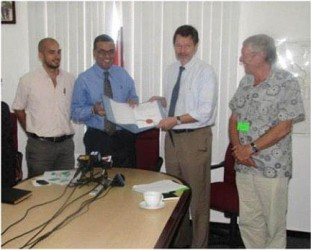 Minister of Natural Resources and the Environment Robert Persaud (second from left) and German Ambassador Stefan Schluter with the note signed. (GINA photo)