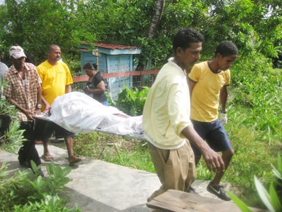 Undertakers moving Jasmattie Pooran's body yesterday morning