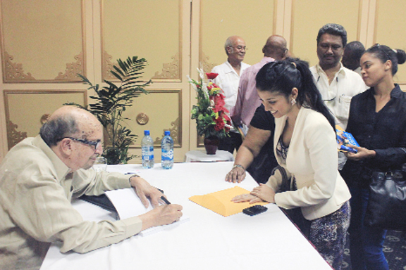 Dr Rudy Insanally autographs a book at the launch on Friday
