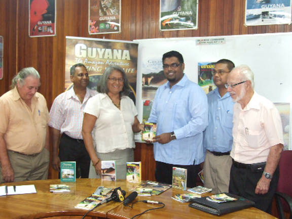 "Acting Tourism Minister Irfaan Ali, publisher of the sixth edition of ""Guyana Where and What,"" Gem Madhoo-Nascimentos, acting THAG President Daniel Gajie, GTA Director Indranauth Haralsingh and other supporters at the launch of the tour guide. (Photo courtesy of the Tourism Ministry)"