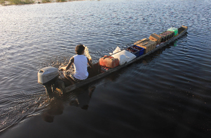 Nishal transporting beverages in his canoe for his mother's shop