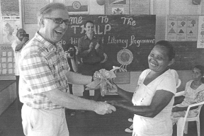 Canadian envoy David Devine smiles broadly as he receives a token from a participant in the recently held Adult Literacy Programme in the North West District. In the background,  volunteers in the programme and other participants look on.