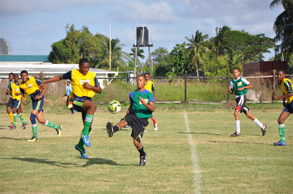 Stephon Rutherford of Queen's College in  battles with a South Ruimveldt Secondary School player for possession.