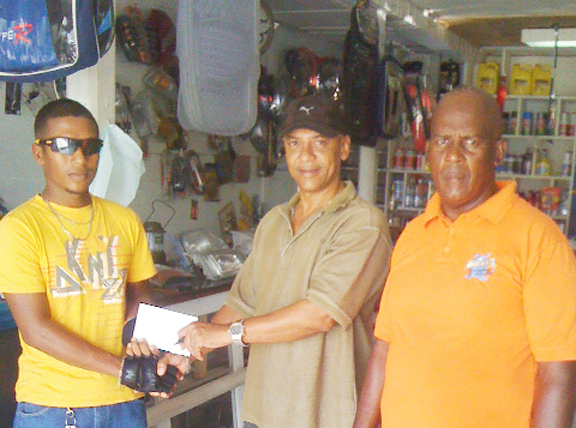 Sponsor and businessman Mark Lewis presenting the monetary donation to rider Neil Reece for his 2012 achievements as Coach Randolph Roberts looks on.