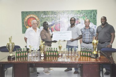 Organiser Marlon Washington in the presence of Banks DIH officials last Friday collects the sponsorship cheque from Premium Beer Brand Manager Jeoff Clement (third right).