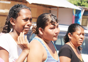 Relatives of Christopher Ramnarine crying as his body was lifted out of a police boat at the Parika Wharf