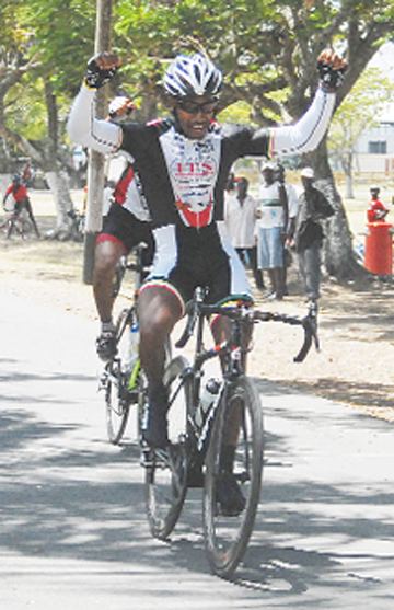 Robin Persaud triumphantly crosses the finish line after one of his 15 victories last year. (Orlando Charles photo)