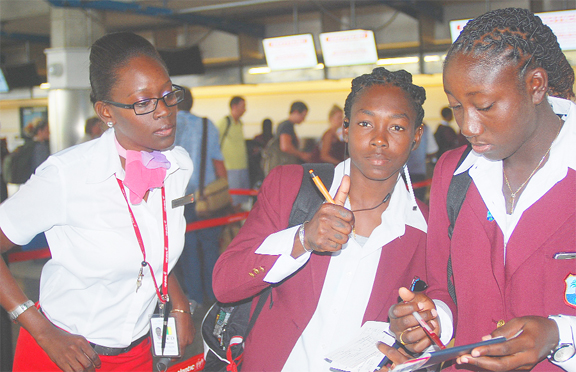 SHEMAINE CAMPBELLE GIVES THE THUMBS UP SIGN! Shemaine Campbelle gives the thumbs up sign as she and Stafanie Taylor get assistance from a Virgin Atlantic staffer as the West Indies women's team departed the region on their way to India for the Women's 2013 World  Cup competition which begins on Thursday. WICB Media Photo/Philip Spooner