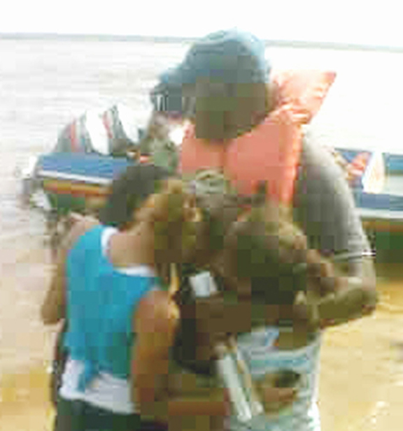 Ricky Amsterdam, father of brothers Keanu Amsterdam and Ricky Bobb, comforts his daughters yesterday after he returned from the search. Keanu Amsterdam's body was recovered yesterday morning.