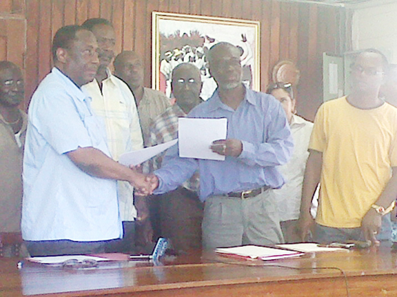 GPSU President Patrick Yarde (left) and GTUC President Norris Witter (third, right) exchange copies of the signed communiqué in the presence of other trade unionists