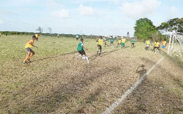 Jeremy Garrett from North Ruimveldt Secondary in green dribbling past his markers in route to scoring against St. Winifred Secondary Milo U20 action between North Ruimveldt Secondary in green and St. Winifred Secondary.