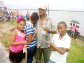 Ricky Bobb's grandfather comforts his siblings shortly after his body arrived in Bartica.