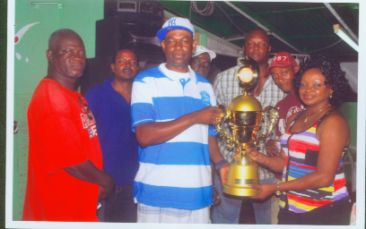 Travis Cameron, left of Mix Up dominoes team receives the trophy from a representative of the sponsor while Linden Boston of Boss Construction is third from right.