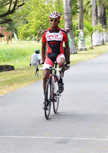 Raynauth Jeffrey triumphantly crosses the finish line at yesterdays Ricks and Sari Agro Industries Limited11-race cycling meet at the National Park circuit, Thomas Lands.