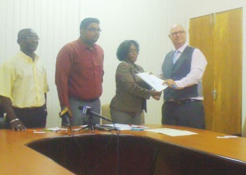 A representative of Harris Paints (right) and a representative of the ministry formalize the arrangement.