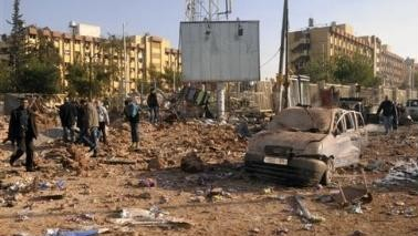 Syrian security personnel and civilians gather at the site where two explosions rocked the University of Aleppo in Syria's second largest city, January 15, 2013. REUTERS/George Ourfalian