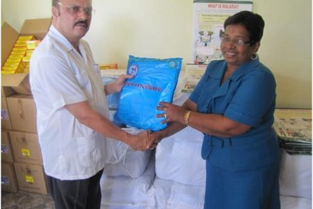 Minister of Health Dr Bheri Ramsaran (left) presents an insecticide–treated net to Regional Health Officer, Region Seven, Merlene Ferrier. The Region received 5, 000 of the nets. (GINA photo)