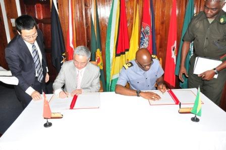 In this GDF photo Ambassador Zhang Limin (second from left) and Commodore Gary Best sign the protocol.