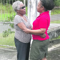 Marjorie Tsoi-a-Fatt , left, comforts her daughter Denise Tsoi-a-Fatt-Angus yesterday in Tobago (Trinidad Express photo)