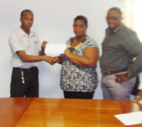 Quacy Coates of NCN hands over the sponsorship cheque on behalf of his company to Angela Haniff of the Berbice Cricket Board as NCN CEO Michael Gordon looks on.