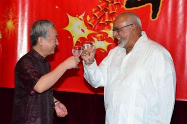 Chinese Ambassador Zhang Limin (left) and President Donald Ramotar toast to celebrate the Chinese New Year. (GINA photo)