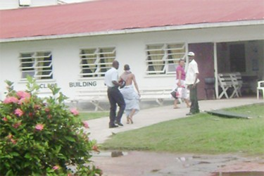 The tortured teen (second, left) with a sheet wrapped around his waist being escorted into the West Demerara Regional Hospital by a policeman. (Stabroek News file photo)