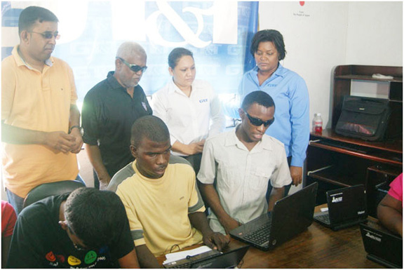 Students demonstrating the software to GT&T PROs Allison Parker (right, standing) and Nadia De Abreu (second, right) in the presence of Chairman Cecil Morris (second left, standing) and other members of the society.