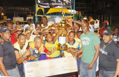 The Plaisance Football team displays the Guinness Greatest of the Street trophy with their supporters very much in evidence.