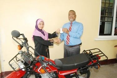 Prime Minister Sam Hinds (right) handing over the keys to the bike to Rosie George. (GINA photo)