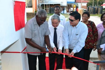 Minister Robeson Benn (left) in his capacity as acting Foreign Affairs Minister cutting the ceremonial ribbon to commission the new CCTV channel. He is assisted by China's Ambassador to Guyana, Zhang Limin (centre) and Chairman of the board of the National Communications Network, Dr. Prem Misir. (GINA photo)