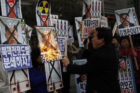 "An activist from an anti-North Korea civic group burns a portrait of North's leader Kim Jong-un during a rally against North Korea's nuclear test near the U.S. embassy in central Seoul February 12, 2013. The placards read, ""Let's pulverize North Korea's nuclear war provocations!"" (L) and ""Kim Jong-un out!"" (R) REUTERS/Kim Hong-Ji"