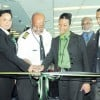 (From left) Director of Tourism John Lynch (face hidden) watches as observes Kayla Reece (second left), her father Captain Ron Reece, Chairman/CEO of Fly Jamaica, and Ann Marie Thomas, Fly Jamaica's Area Manager for the New York region cut the ribbon ceremonially marking the inaugural flight of Fly Jamaica Airways inside the departure lounge of the John F Kennedy International Airport in New York, last Thursday. Looking on are Herman LaMont, Jamaica's Consul General to New York and Will Rogers (right) consultant to Fly Jamaica. (Jamaica Observer photo)