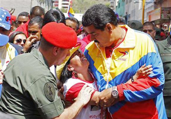 Venezuela's Vice President Nicolas Maduro consoles a supporter of deceased Venezuelan leader Hugo Chavez, as his coffin is driven through the streets of Caracas, yesterday. REUTERS/Carlos Garcia Rawlins