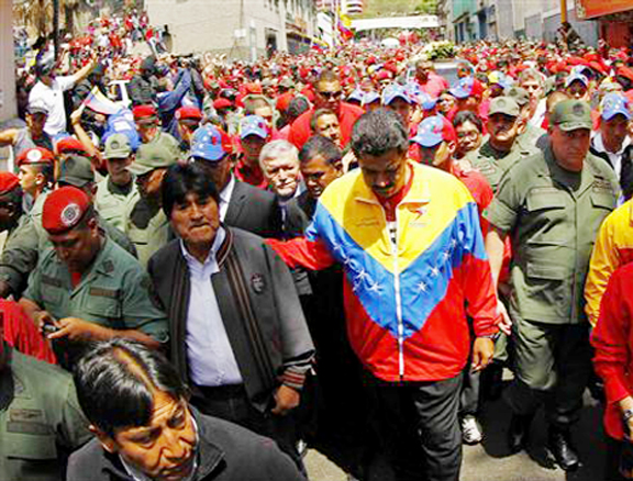 Venezuela's Vice President Nicolas Maduro (R) and Bolivian President Evo Morales (2nd L) walk ahead of the vehicle carrying the coffin of deceased Venezuelan leader Hugo Chavez, as it is driven through the streets of Caracas after leaving the military hospital where he died of cancer in Caracas yesterday. REUTERS/Carlos Garcia Rawlins