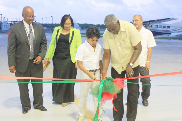 A young man assisting Minister of Works Robeson Benn in cutting the ribbon to commission the Wings Aviation Limited hangar at Ogle International Airport. Looking on (from left to right) are CEO of Wings Aviation Ronald Reece, his wife Roxanne who is the General Manager and Director General of the Guyana Civil Aviation Authority Zulficar Mohamed.