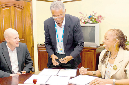 Chief Executive Officer of e- Learning Jamaica Ltd Avrill Crawford shares a light moment with Peter Williams of Nelson Thornes. Occasion was last Thursday's signing of a contract to provide the e-textbook Geography for CSEC at the offices of e- LJam. At centre is Robert Philips, education specialist at e-LJam. (Jamaica Observer photo)