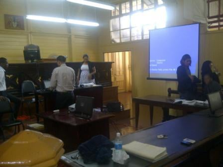 The courtroom for today's hearing. The screen is at right.