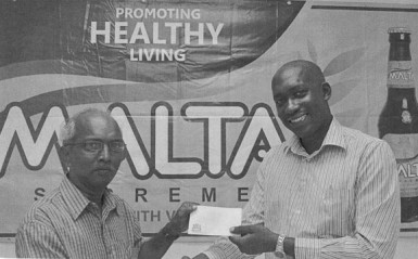 Brand Manager at Banks DIH Clayton McKenzie (right) presents a sponsorship cheque to Secretary of the Guyana Chess Federation Vishnu Rampersaud (left) at Thirst Park.