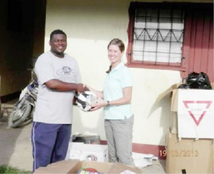 A representative (left) of the Linden group receiving the donation. (US embassy photo)