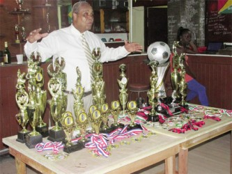 (Linden Town Week): Howell 'Yellowman' Hinds stands behind the trophies and medals at the Senior Supervisors Club (SSC), Linden.