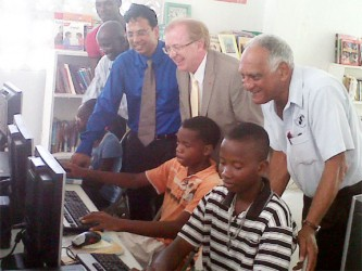 From left to right, Robin Phillips, GT&T CEO Radha Krishna Sharma, Canadian High Commissioner David Devine and Lenny Shuffler look on as youths from the Buxton Youth Development Centre use the computers that were donated.