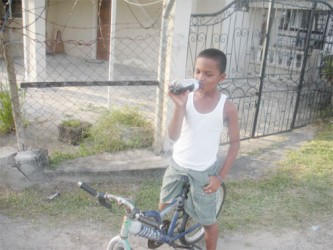 Young lad sipping on a cold drink