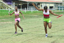 Victory! Leota Babb of Police Progressive Youth Club captures the female 4x100m relay event with a dip at the finish line ahead of Mercury Fast Laner's Ebony Nelson yesterday afternoon at the Police Sports Club ground, Eve Leary.