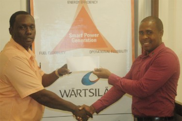Contracts Manager at Wartsila, Arron Fraser presents Athletics Association of Guyana Vice-President Gavin Hope with the incentives for the Youth/Junior Championship on Monday at Wartsila, Kingston.