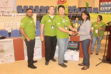 Programmers from the winning team, Sirca, receiving their trophy from Dr Sita Shah-Roth. From left are team members Amanauth Persaud, Jason Plummer and Richard Cheng-Yuen